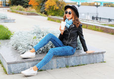 Fashion cool smiling girl with coffee cup wearing black rock jacket, hat resting in the city park Royalty Free Stock Photo