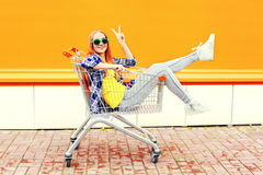 Fashion cool smiling girl having fun sitting in shopping trolley cart. Over colorful background Royalty Free Stock Photography