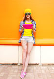 Fashion cool smiling girl using tablet pc over colorful orange Royalty Free Stock Image