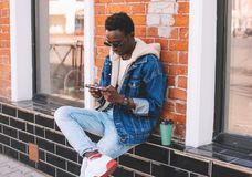 Fashion cool urban african man with smartphone sitting on city street royalty free stock photography