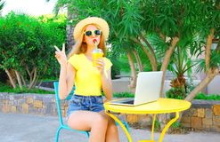 Fashion cool woman drinks fruit juice with laptop computer Royalty Free Stock Photos