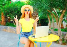 Fashion cool woman is having fun sits at a cafe table with laptop Royalty Free Stock Images