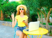 Fashion cool woman is having fun sits at a cafe table with smartphone Royalty Free Stock Images