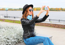 Fashion cool young smiling girl taking picture self portrait on smartphone in city Stock Images