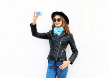 Fashion cool young smiling girl taking picture self portrait on smartphone in city wearing black rock jacket, hat over white Royalty Free Stock Images