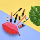 Fashion Cosmetic Makeup Set. Beauty Essentials. Fashion Cosmetic Makeup Minimal Set. Creative Essentials. Trendy Design Pink Red Clutch Bag, tropical leaf Stock Photo