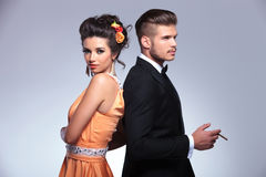 Fashion couple back to back and man smoking Royalty Free Stock Images