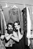 Fashion couple in closet. Fashion couple denuded of brunette girl and bearded men choose clothes to wear near rack with hangers in wardrobe closet stock photo