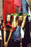 Fashion couple in closet. Fashion couple denuded tired of brunette girl with red hangers and bearded men with green high heels shoes among clothes to wear near royalty free stock images