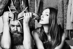 Fashion couple in closet. Fashion couple denuded tired of brunette girl with long hair and bearded men with green high heels shoes among clothes to wear near stock image