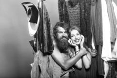 Fashion couple in closet. Fashion couple denuded of brunette girl and bearded men choose clothes to wear near rack in wardrobe closet stock images
