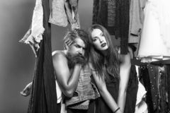 Fashion couple in closet. Fashion couple denuded of brunette girl and bearded men choose clothes to wear near rack in wardrobe closet royalty free stock image