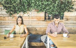 Fashion couple in disinterest moment ignoring each other using phone. Fashion couple in disinterest moment ignoring each other using mobile cell phone - Concept Royalty Free Stock Images