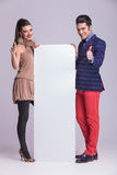 Fashion couple holding a white board Royalty Free Stock Photos