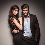 Fashion couple leaning on a dark grey wall Royalty Free Stock Image