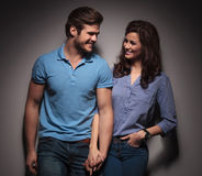 Fashion couple leaning on a grey wall while holding hands Stock Photo