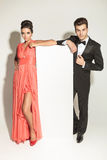 Fashion couple leaning on a white empy board Stock Image