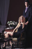 Fashion couple in low key. Portrait of a fashion couple in low key. Elegant blond women seated Royalty Free Stock Photos