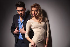 Fashion couple posing near a grey wall Royalty Free Stock Images