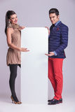 Fashion couple presenting a white empty bilboard. Full body picture of a young fashion couple presenting a white empty bilboard royalty free stock image