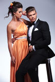 Fashion couple with seated man looking away Stock Photography
