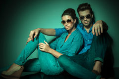 Fashion couple sitting and leaning on a wall. Young fashion couple sitting and leaning on a wall while looking at the camera Royalty Free Stock Photos
