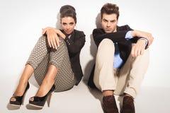 Fashion couple sitting on studio background Royalty Free Stock Photos