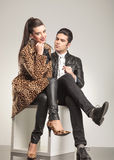 Fashion couple sitting on a white cube Royalty Free Stock Image