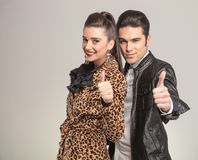 Fashion couple smiling and showing the thumbs up gesture. Picture of a young fashion couple smiling at the camera while showing the thumbs up gesture Royalty Free Stock Photo