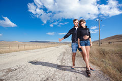 Fashion couple try to stop the car on old road Royalty Free Stock Image