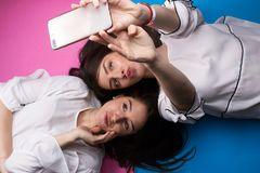 Fashion crazy girls making selfie. Inside cute sisters cool fun Stock Photo
