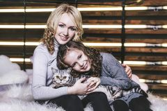 Fashion cute little girl and beautiful woman with a British kitt Stock Photography