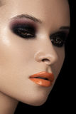 Fashion dark smoky eyes makeup, black eyeshadows, orange lips. Close-up beauty portrait of attractive model face with bright make-up. Dark smoky eyes makeup stock photography
