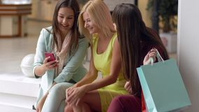 Fashion day, attractive shopaholics women record video on smartphone while shopping with packages in hands during sales. Season and discounts on black friday in stock video footage