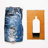Fashion design grunge style. Vintage blue jeans and white bottle Royalty Free Stock Image