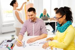Fashion designers drawing sketches at studio. Fashion design, tailoring and people concept - team of designers drawing sketches at studio royalty free stock photography