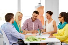 Team of fashion designers working at office. Fashion design, tailoring and people concept - team of fashion designers with sketch working at office royalty free stock photography