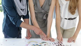 Fashion design team looking at costume jewelry and model contact sheet Stock Photos
