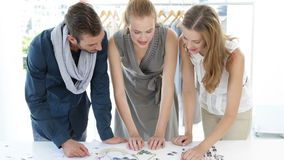 Fashion design team looking at costume jewelry Stock Photos