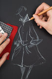 Fashion designer. Is drawing a fashion sketch Stock Images