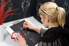 Fashion designer. Is drawing a fashion sketch Stock Photos