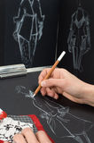 Fashion designer. Dressmaker is drawing a fashion sketch Stock Images