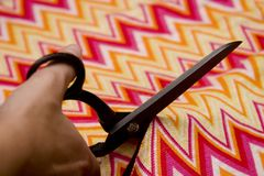 Fashion Designer. Scissor cutting fabric in fashion designer atelier stock images