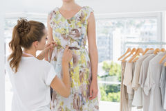 Fashion designer adjusting dress on model Royalty Free Stock Image
