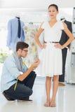 Fashion designer adjusting dress on model Royalty Free Stock Photos