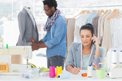 Fashion designer calling and writing Stock Photo