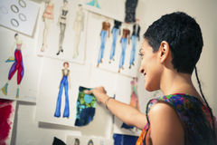 Fashion designer contemplating drawings in studio. Young people and small business, hispanic woman at work as fashion designer and tailor, looking at sketches of