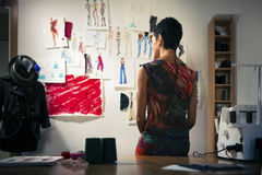 Fashion designer contemplating drawings in studio. Young people and small business, hispanic woman at work as fashion designer and tailor, looking at sketches of Royalty Free Stock Photos