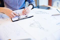 Fashion designer creating new clothes and drawing sketches on clipboard Stock Photo