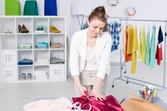 Fashion designer cutting fabric in an office royalty free stock photography